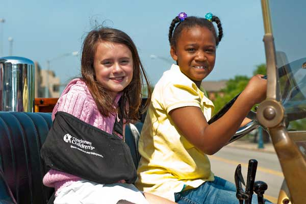 Two girls riding in a motorcade